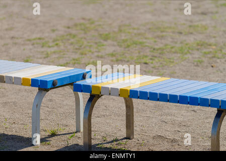 A blue, yellow and white bench on the side of a sports field. - Stock Photo