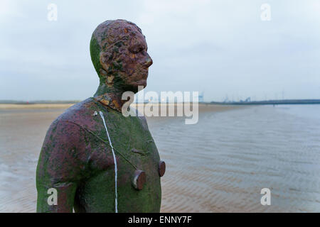 One of the statues in the Another Place installation by Antony Gormley on Crosby Beach, Liverpool, England. - Stock Photo