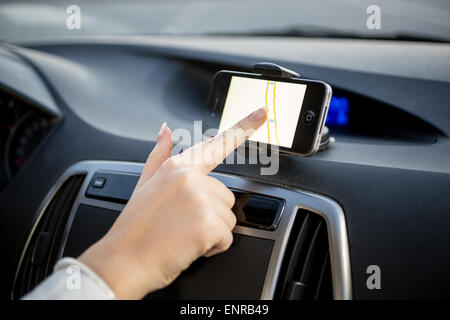 Female driver using touchscreen smartphone with GPS navigation - Stock Photo