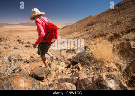 Africa, Namibia. Tok Tokkie Trails. Woman decending rocks. - Stock Photo