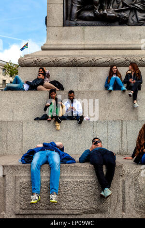 People Sitting On The Base Of Nelson's Column In Trafalgar Square During The 70th Anniversary of VE Day Celebrations, - Stock Photo