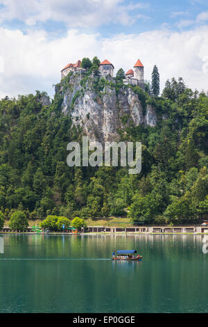 Lake Bled, Upper Carniola, Slovenia.  Bled Castle seen across the lake. Tourists enjoying boating excursion. - Stock Photo