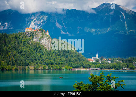 Lake Bled, Upper Carniola, Slovenia.  Bled Castle seen across the lake.  The town of Bled in the background. - Stock Photo
