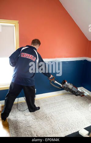 Teen vacuuming newly installed carpet in his bedroom. St Paul Minnesota MN USA - Stock Photo