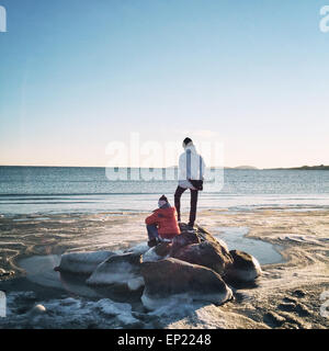 Rear view of two boys on rocks by the sea - Stock Photo