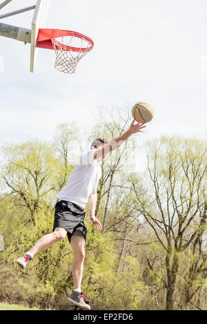 Young man doing basketball trick shots as he leaps through the air - Stock Photo