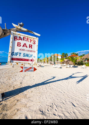 Jamaica, Negril, view to sandy beach with old sign post - Stock Photo