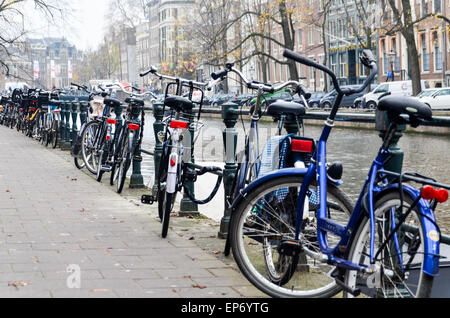 Bicycles parked along a canal in the city centre of Amsterdam, the Netherlands - Stock Photo