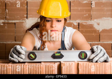 Woman Bricklayer with Helmet Holding a Spirit Level on a Brick Wall - Stock Photo