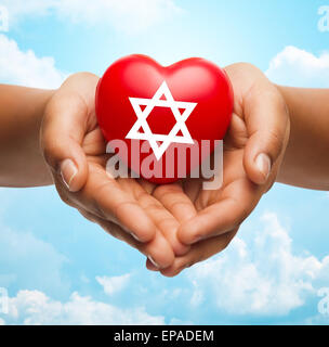 close up of hands holding heart with jewish star - Stock Photo