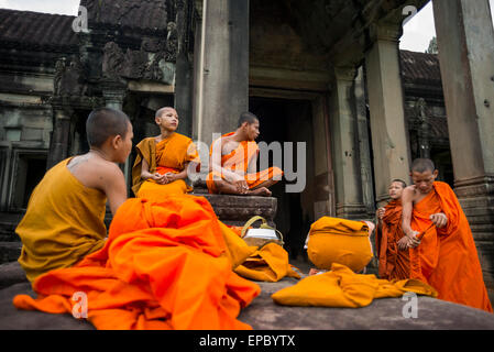 A group of young monks hang out at Angkor Wat; Siem Reap, Cambodia - Stock Photo