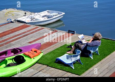 man reading newspaper on dock on Richardson Bay in Sausalito California - Stock Photo