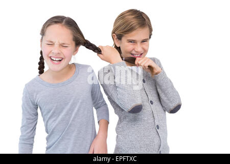 Angry young boy pulling sister hair in a fight - Stock Photo