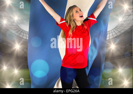 Composite image of cheering football fan in red holding honduras flag - Stock Photo