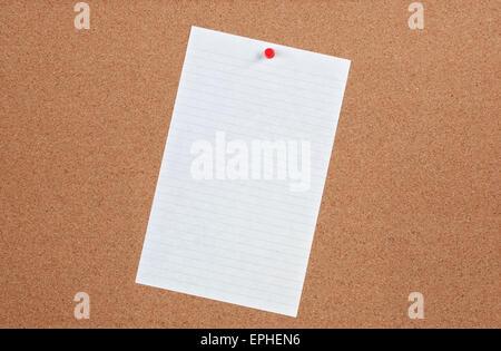 Single sheet of blank note paper pinned on cork board. - Stock Photo