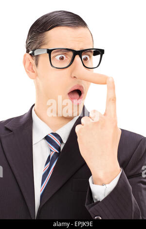 Vertical shot of a young displeased businessman looking at his long nose and trying to put it back with his finger - Stock Photo