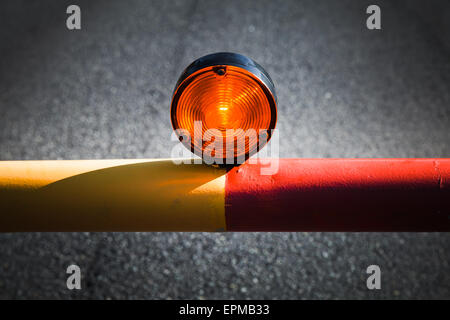 Red light on the automatic barrier, no way signal over dark asphalt road - Stock Photo