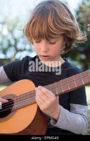 Little boy playing acoustic guitar - Stock Photo