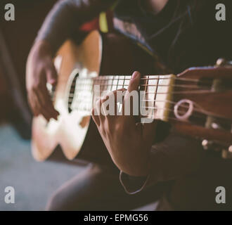 Little boy playing acoustic guitar at home, close-up - Stock Photo