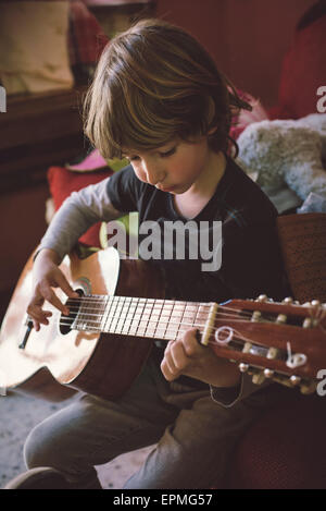 Little boy playing acoustic guitar at home - Stock Photo