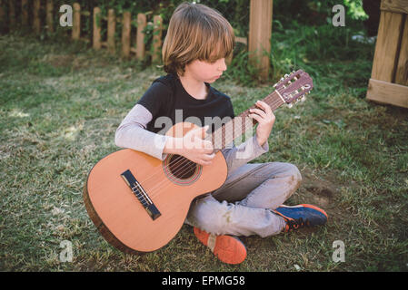 Little boy sitting in the garden playing acoustic guitar - Stock Photo