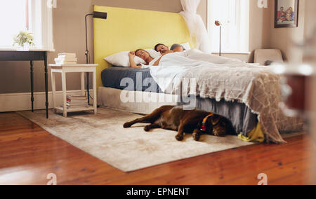 Indoor shot of dog lying on floor in bedroom. Young couple sleeping comfortably on bed. - Stock Photo