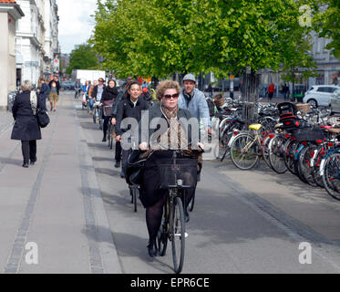 Cyclists on the cycle track along Frederiksborggade towards Nørreport Station in central Copenhagen in late morning - Stock Photo