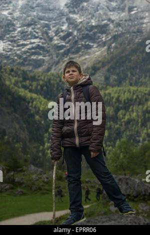 Young boy standing on the rock on a mountain background - Stock Photo