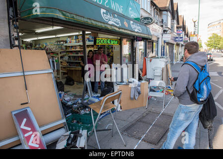 London, UK. 21st May 2015. Owners begin clean up after car crashes through shop front in Wembley. London, UK. Credit: - Stock Photo
