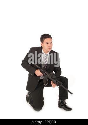 White man kneeling with an AR-15 Semi automatic gun - Stock Photo