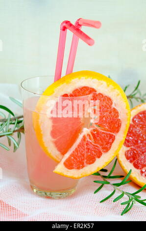 Fresh grapefruit juice in a glass decorated with red grapefruit slice on  a table decorated with rosemary branch - Stock Photo