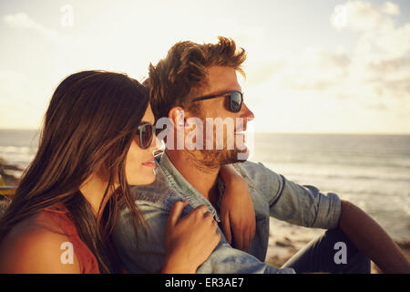 Beautiful young couple together outdoors on a summer day. Caucasian couple enjoying the beach view, both wearing - Stock Photo