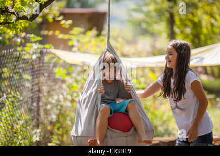 Boy and girl playing on a swing in the garden - Stock Photo