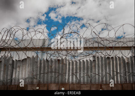 Galvanised high security razor wire and barbed wires deterrent to slow down climbing over walls with mass of corrugated - Stock Photo