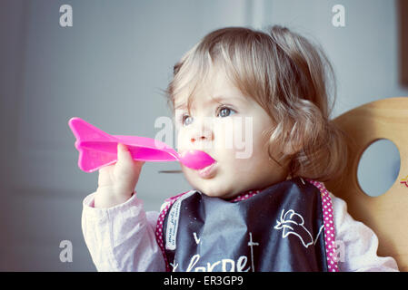 Baby girl feeding herself - Stock Photo