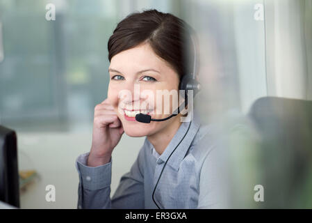 Businesswoman wearing headset during conference call, portrait - Stock Photo