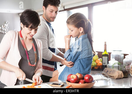 Family preparing food together in kitchen - Stock Photo