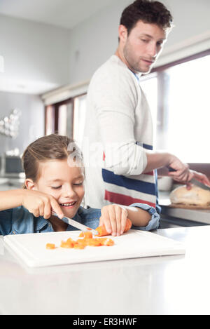 Little girl helping her father prepare food in kitchen - Stock Photo