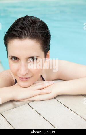 Woman relaxing in pool, portrait - Stock Photo