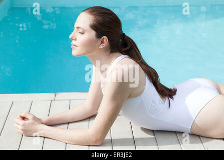 Young woman sunbathing beside pool with eyes closed - Stock Photo