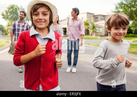 Boys running outdoors, family in background - Stock Photo