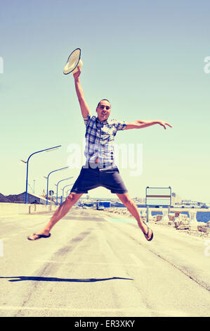a young caucasian man with a straw hat in his hand jumping in a no traffic road near the sea - Stock Photo