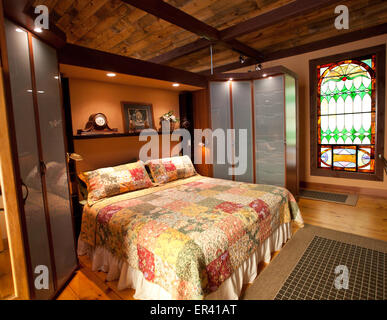 Interior detail of master bedroom. Vermont dairy barn renovated into a unique home featuring antique stained glass - Stock Photo