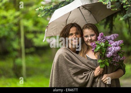 Mother with her daughter in the Park in the rain together under an umbrella. - Stock Photo