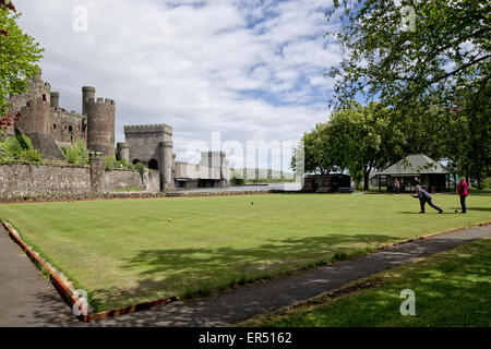 Crown green bowls below Conwy's medieval Castle with the entire span of Stephenson's railway bridge in the background - Stock Photo