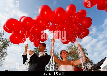 Bridal couple let  gas-filled red balloons fly, Bavaria, Germany - Stock Photo