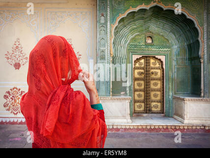 Woman in red scarf looking at green gate door in City Palace of Jaipur, Rajasthan, India - Stock Photo