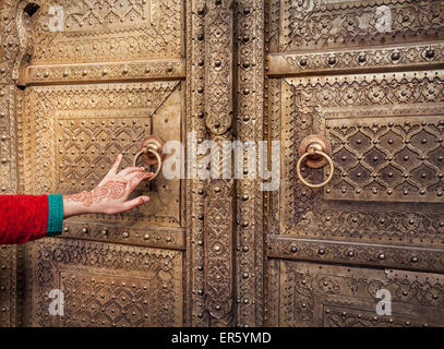 Woman hand with henna painting opening golden door in City Palace of Jaipur, Rajasthan, India - Stock Photo