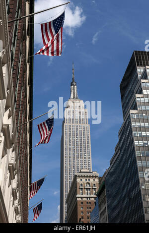 Empire State Building, US flags on a building, Manhattan, New York, USA - Stock Photo