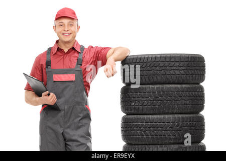 Young male mechanic in a gray jumpsuit leaning on a stack of tires and holding a clipboard isolated on white background - Stock Photo